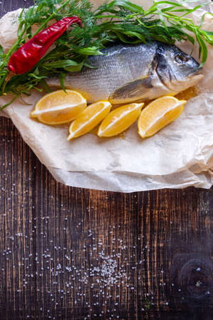 Fish dorado with lemon, hot pepper and aromatic herbs prepared for grilling Stok Fotoğraf