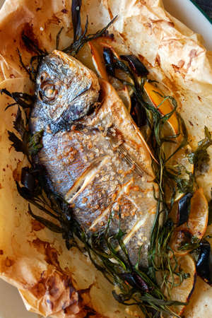 Baked dorado fish with lemon and rosemary and sea salt close-up. Stok Fotoğraf