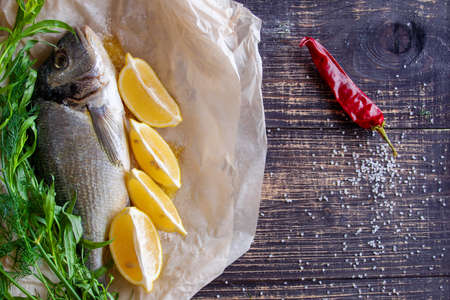 Fresh fish dorado with lemon, spices and herbs prepared for grilling
