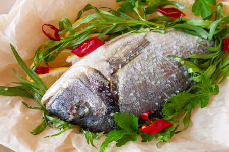 Dorada with lemon, pepper and aromatic herbs prepared for baking close-up