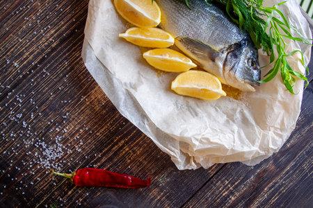 Fresh dorada fish with lemon, hot pepper and aromatic herbs prepared for baking Stok Fotoğraf
