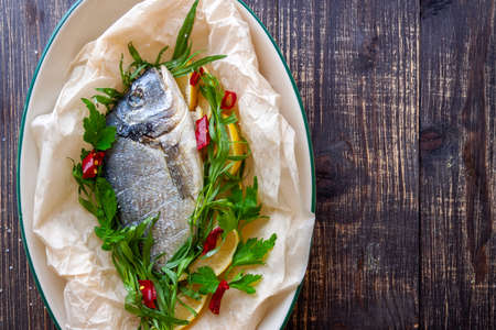 Dorada with lemon, pepper and herbs close-up on a wooden background