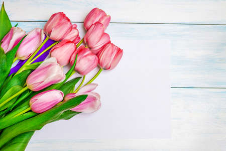 Bouquet of pink tulips on a white wooden background with a white sheet of paper. Stok Fotoğraf