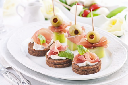 Canapes with ham and green pickled olives photo