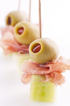 tapas españolas: canapés con aceitunas en conserva y el melón