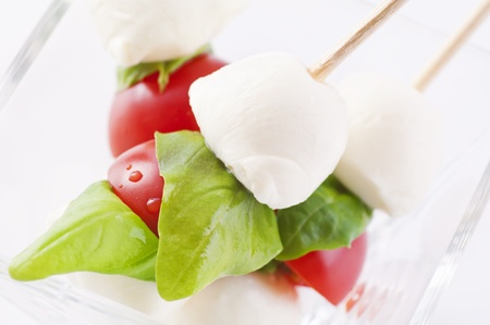 Tomato mozzarella with fresh basil as closeup photo