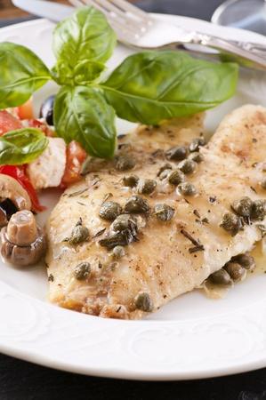 tilapiini: Fish piccata with salad  Stock Photo