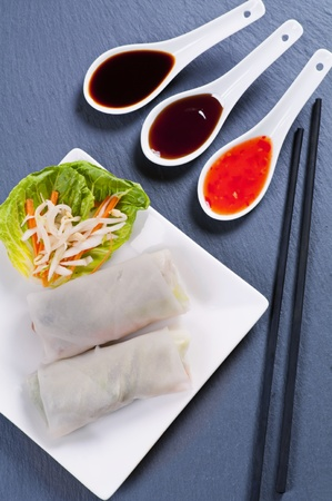goi: Spring rolls with sauces on black background Stock Photo