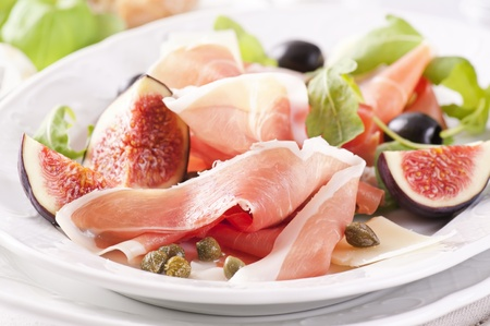 Prosciutto with capers, olives and figs photo