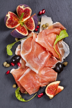 cured ham: Tapas on a black plate