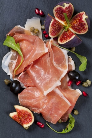 cured ham: Tapas with prosciutto on a black plate
