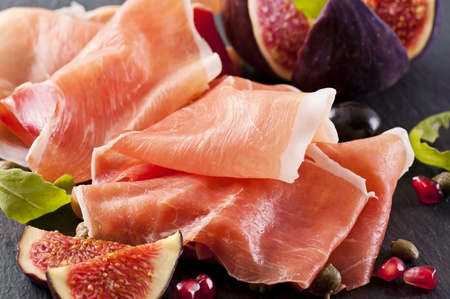 antipasto: Prosciutto with figs on a black plate Stock Photo