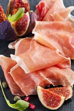 Prosciutto with fig on a black plate  photo