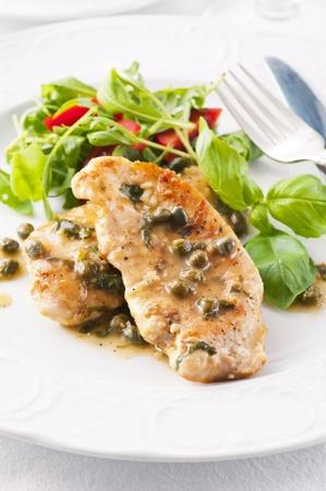 Huhn Piccata mit Kapern und Salat Standard-Bild