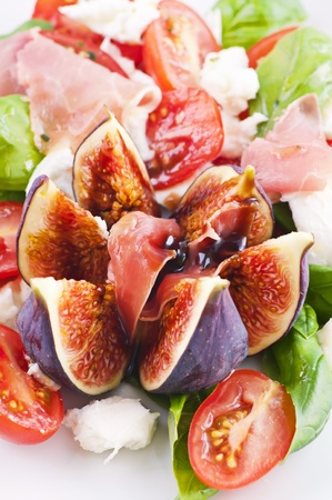 Fig with salad and prosciutto as starter photo
