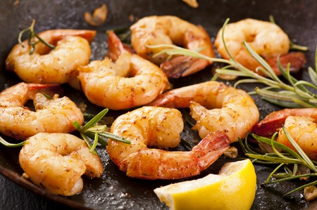 fried prawns with fresh rosemary and lemon juice Stock Photo