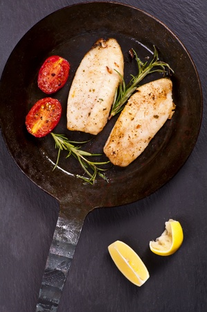 fish fillet fried with fresh herbs in a pan photo