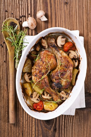 Chicken legs roasted with the mushrooms and potato photo