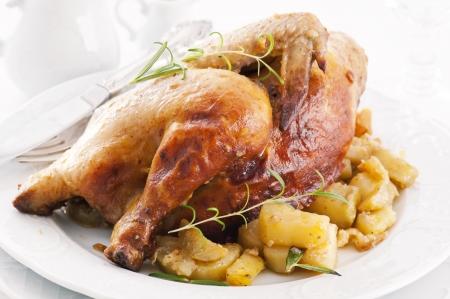 cockerel: pollo arrosto con patate ed erbe Archivio Fotografico