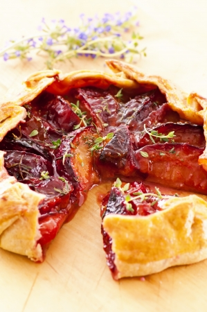 Tart with plums and fresh herbs photo