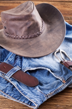 effloresce: Jeans and leather hat on a wood board Stock Photo