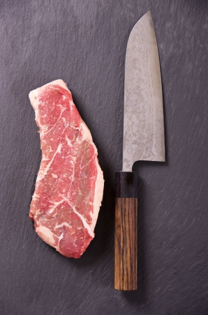 beef steak with japanese santoku knife photo