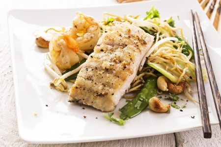 fired fish with noodles and vegetables photo