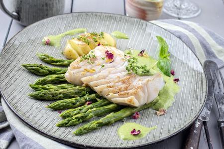 plato de pescado: filete de carbonero con espárragos verdes