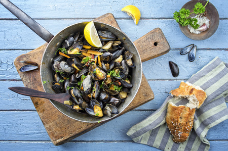 wooden table top view: Sailors Mussel in Casserole Stock Photo