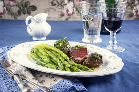 Medallions with green asparagus on plate