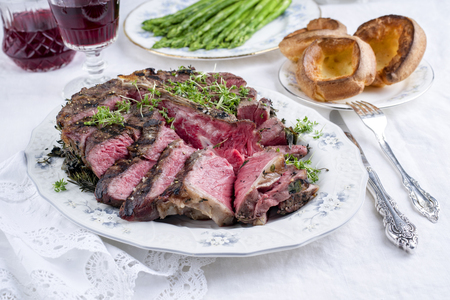 Sliced ??porterhouse steak with yorkshires and green asparagus on plate