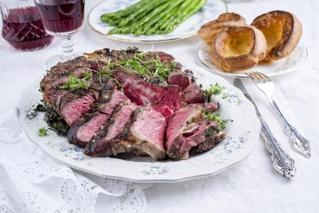 porterhouse: Sliced Porterhouse Steak with Yorkshires and Green Asparagus on Plate Stock Photo