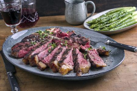 Wagyu T-Bone Steak con asparagi verdi sulla piastra Archivio Fotografico - 69668119