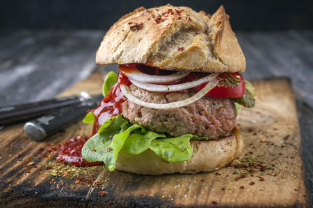 semmel: Barbecue Hamburger with Tomato and Salad Leaf on old Cutting Board