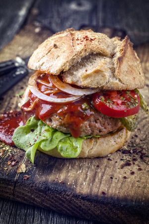 semmel: Barbecue Hamburger with Tomato and Lettuce Leaf on old Cutting Board Stock Photo