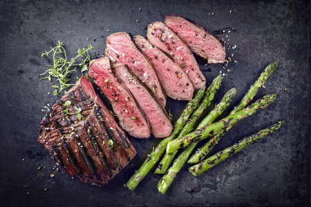Barbecue Point Steak with Green Asparagus on old Sheet