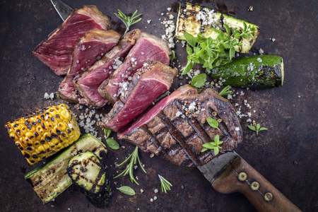 rumpsteak: Barbecue Roast Beef with Vegetable on old Metal Sheet Stock Photo