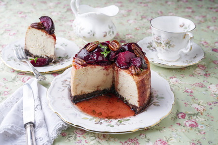 gold table cloth: Cheesecake with Plum and Pecan Nut on Plate Stock Photo