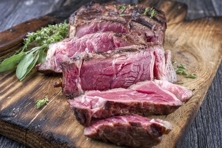 black angus cattle: Barbecue rib eye steak sliced ??on cutting board