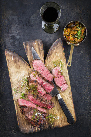 rumpsteak: Barbecue Point Steak on old Cutting Board Stock Photo