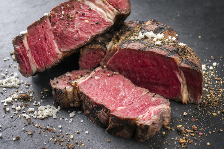 Barbecue dry aged Wagyu rib eye steak as close-up on a slate Stock Photo
