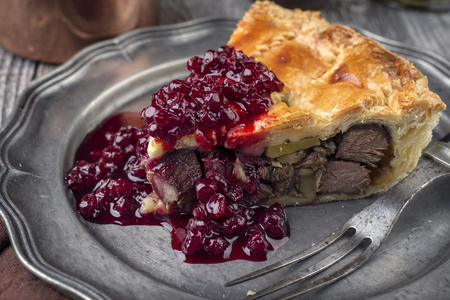 Venison Pie with Cranberry Relish as close-up on a pewter plate Stock Photo