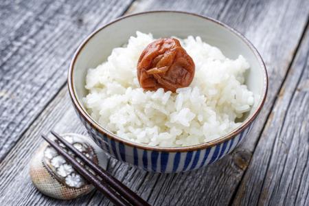 ボウルにクローズ アップとして梅干しと伝統的な日本のコシヒカリ 写真素材