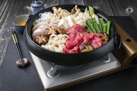 ei: Traditional Sukiyaki pot with Kobe Beef and Vegetable as close-up on slate