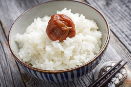 culinary arts: Traditional Japanese Koshihikari Rice with Umeboshi as close-up in a bowl