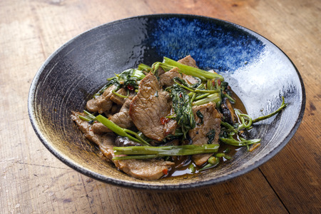 soja: Traditional Stir Fried Thai Pad Nua with Morning Glory as close-up in a bowl