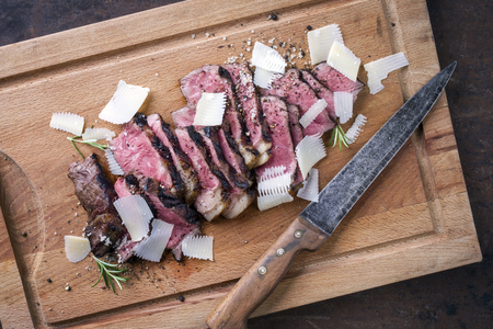 Traditional Italian Tagliata Steak with Parmesan as close-up on cutting board