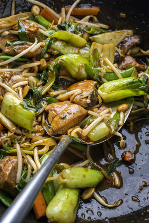 Traditional stir fried Chicken Gung Bao with Vegetable as close-up in Wok