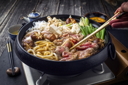 dashi: Cooking traditional Sukiyaki pot with Kobe Beef and Vegetable as close-up on slate Stock Photo