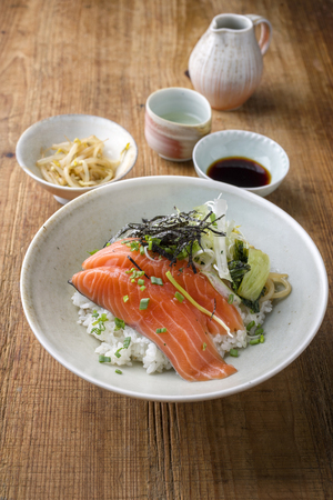 thinly: Traditional Japanese Hokkaidon Thinly sliced salmon Donburi as close-up in a bowl Stock Photo